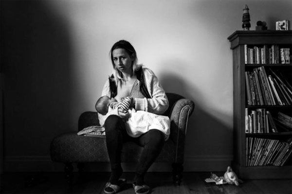 'The first photo I took was this one, it's a self-portrait of me breastfeeding my son Xavier. This is pretty much what I look like when I'm breastfeeding most of the time. I then put out a call out to see if other women might be interest in being photographed in the same way. The response has been incredible – so many women have offered their time and told me how relieved they are to see realistic images of women breastfeeding.' Source: Suzie Blake/What Does Breast Feeding Look Like