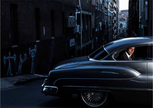 Photographing Houda in one of his beloved vintage cars at dusk in Surry Hills, Walker gives his subject an allure that is slightly cold, tough, and a bit mysterious. Source: Nic Walker/Walkleys