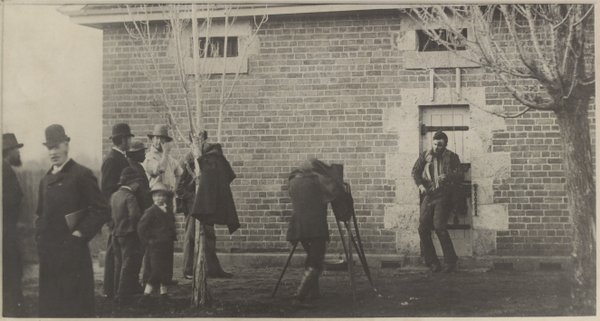 Joe Byrne's body outside Benalla Police Station, sepia photograph by JW Lindt, 29 June 1880. The man holding the sketch book to the left would draw illustrations for the paper. This photographer was shooting for police. Source: Supplied/State Library Victoria Pictures Collection.